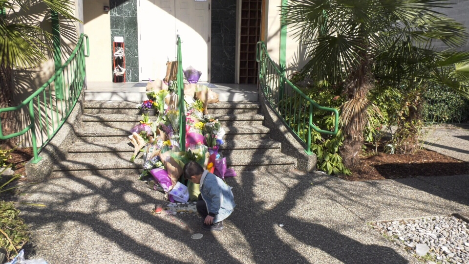 A young boy drops off flowers in front of a Vancouver mosque.