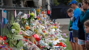 Mourners lay flowers on a wall at the Botanical Gardens in Christchurch, New Zealand, Saturday, March 16, 2019.  (AP Photo/Vincent Thian)