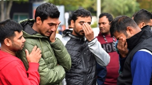 Friends of a missing man grieve outside a refuge center in Christchurch, Sunday, March 17, 2019. (Mick Tsikas/AAP Image via AP)