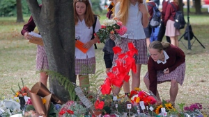 Students pay their respects at a park outside the Al Noor mosque in Christchurch, New Zealand, Monday, March 18, 2019. Three days after mosque shootings, New Zealand's deadliest shooting in modern history, relatives were anxiously waiting for word on when they can bury their loved ones. (AP Photo/Vincent Yu)