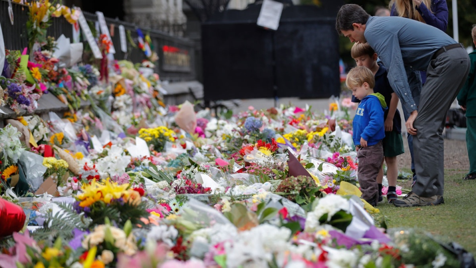 Mourners lay flowers on a wall at the Botanical Gardens in Christchurch, New Zealand, Monday, March 18, 2019. (AP Photo/Vincent Thian)