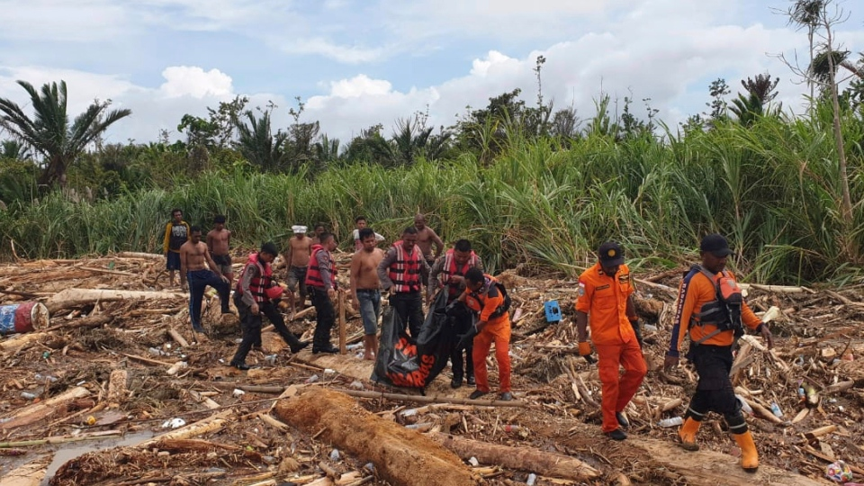 In this photo provided by National Search and Rescue Agency (BASARNAS), the agency's personnel and police carry the body of flood victim at Sentani, Papua Province, Indonesia, Sunday, March 17, 2019. (BASARNAS via AP