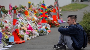 A student pays his respects at a park outside the Al Noor mosque in Christchurch, New Zealand, Monday, March 18, 2019. (AP Photo/Vincent Yu)