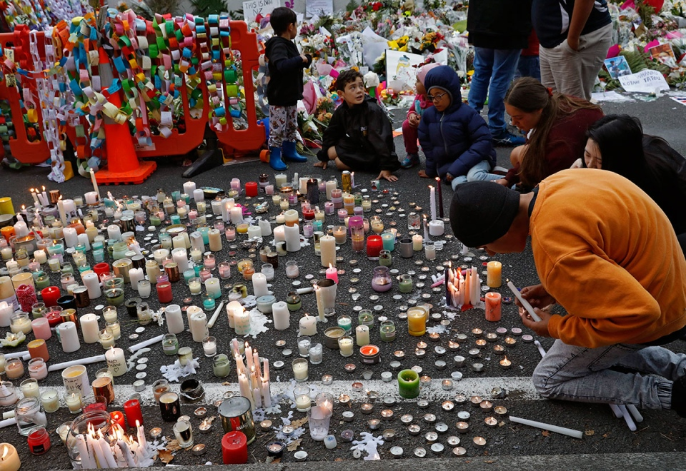 Students light candles as they gather for a vigil to commemorate victims of Friday's shooting, outside the Al Noor mosque in Christchurch, New Zealand, Monday, March 18, 2019. (AP Photo/Vincent Yu)