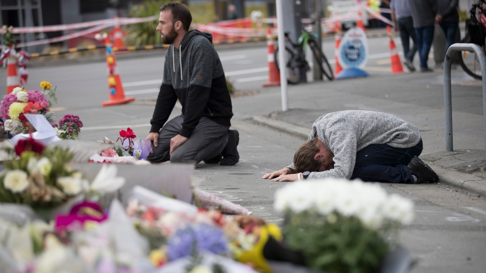 Mourners pray near the Linwood mosque in Christchurch, New Zealand, Tuesday, March 19, 2019. (AP Photo/Vincent Thian)