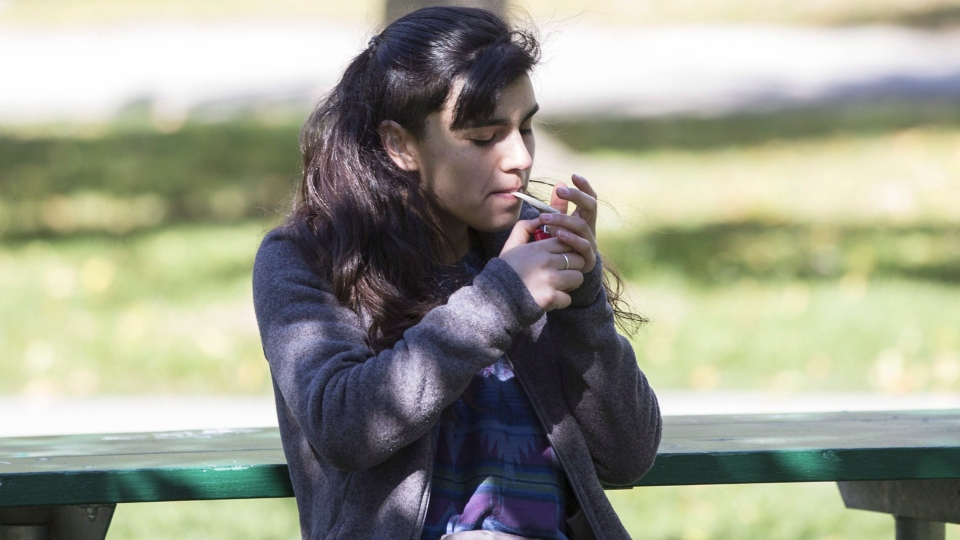 A woman smokes cannabis in a Toronto park on first day of legalization of cannabis across Canada on October 17, 2018. (THE CANADIAN PRESS/Chris Young)