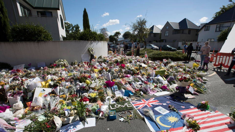 Flowers are placed outside the Al Noor mosque in Christchurch, New Zealand, Monday, March 18, 2019. (AP Photo/Vincent Thian)