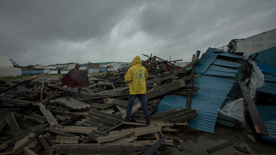 In this photo taken Saturday March 16, 2019 and provided by CARE, people walk through debris on the streets of the city of Beira, Sofala Province, Mozambique, after Cyclone Idai made land fall. The nation's president Filipe Nyusi said more than 1,000 may have been killed by the cyclone. (Josh Estey/CARE via AP)