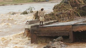 A man stands on the edge of a collapsed bridge in Chimanimani, Zimbabwe, on March 18, 2019. (Tsvangirayi Mukwazhi / AP)