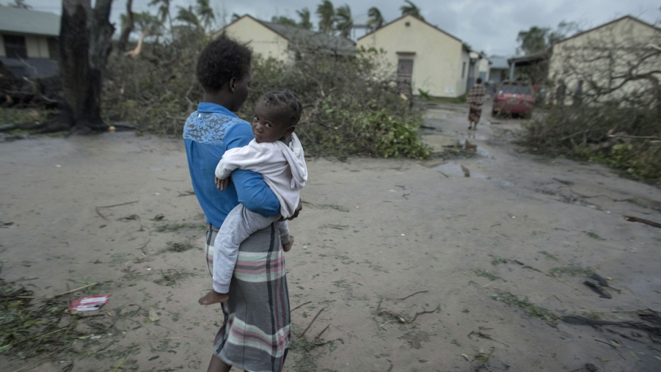A woman and child near a school building being used as emergency shelter in the coastal city of Beira, Mozambique, on March 17, 2019. (Josh Estey/CARE via AP)