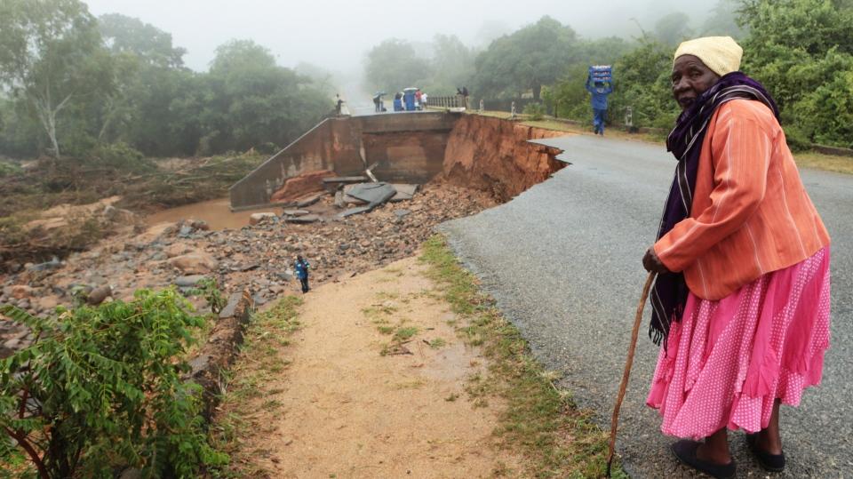 An elderly woman stands next to a collapsed bridge in Chimanimani, about 600 kilometers southeast of Harare, Zimbabwe, Monday, March 18, 2019. (AP Photo/Tsvangirayi Mukwazhi)