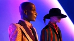 """In this Thursday, March 14, 2019, photo, a suit worn by David Bowie, left, is displayed next to an ensemble worn by Jimi Hendrix for the """"Gender Bending Fashion"""" exhibition at the Museum of Fine Arts in Boston. (AP Photo/Charles Krupa)"""