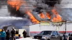 Flames and thick black smoke shoot from a commercial building in New Minas, N.S., on March 19, 2019. (Bill Roberts/submitted)