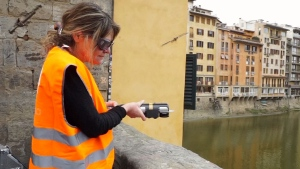 A volunteer cleans graffiti off Pointe Santa Trinita in Florence, Italy, using a special laser cleaning device.