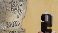 A volunteer uses a 'Laser Blaster' device to clean graffiti off Pointe Santa Trinita in Florence, Italy.
