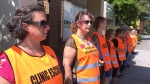 FILE - In this July 17, 2017 file photo, escort volunteers line up outside the EMW Women's Surgical Center in Louisville, Ky. Abortion-rights defenders have expanded their legal fight against Kentucky to try to block the state's most restrictive abortion measure, which would mostly ban the procedure once a fetal heartbeat is detected. (AP Photo/Dylan Lovan, File)