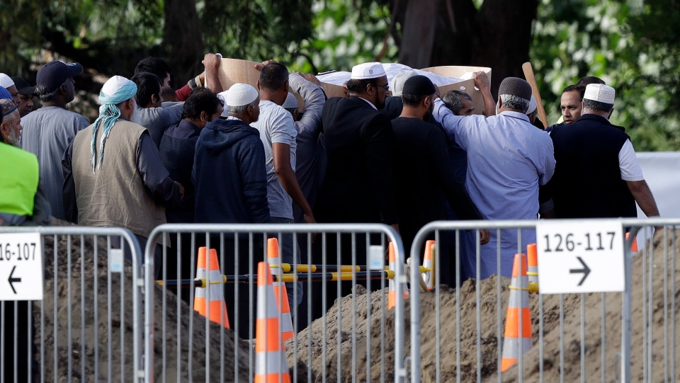 Mourners carry the body of a victim of Friday March 15 mosque shootings for a burial at the Memorial Park Cemetery in Christchurch, New Zealand, Wednesday, March 20, 2019. (AP Photo/Mark Baker)