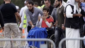 Zaed Mustafa, in wheelchair, brother of Hamza and son of Khalid Mustafa, reacts during the burial at the Memorial Park Cemetery in Christchurch, New Zealand, on March 20, 2019. (Mark Baker / AP)