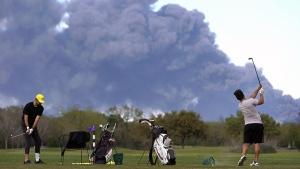 Golfers practice at the Battleground Golf Course driving range as a chemical fire at Intercontinental Terminals Company sends dark smoke over Deer Park, Texas, on March 19, 2019. (Melissa Phillip / Houston Chronicle via AP)