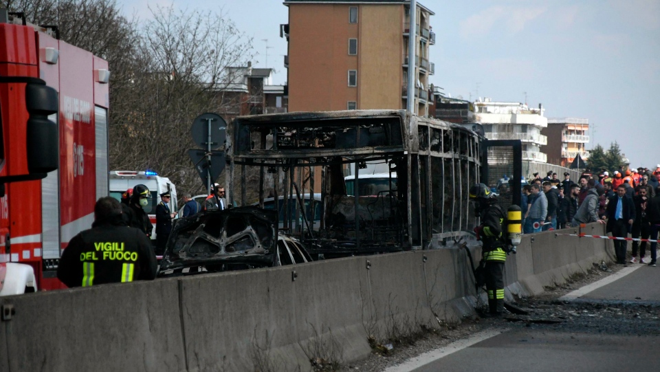 Firefighters stand by the gutted remains of a bus in San Donato Milanese, near Milan, Italy, March 21, 2019. (Daniele Bennati/ANSA via AP)