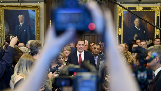 Conservative leader Andrew Scheer speaks to reporters with his caucus surrounding him after leaving Minister of Finance Bill Morneau's budget speech in protest to the handling of the SNC Lavalin scandal in the foyer of the House of Commons on Parliament Hill in Ottawa on Tuesday, March 19, 2019. THE CANADIAN PRESS/Justin Tang