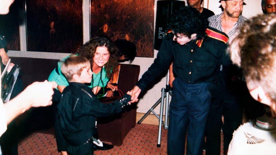 This image released by HBO shows a young Wade Robson shaking hands with pop icon Michael Jackson in 1987, in a scene from the documentary