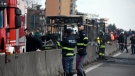 Firefighters and police officers stand by the gutted remains of a bus in San Donato Milanese, near Milan, Italy, March 21, 2019. Italian authorities say a bus driver transporting schoolchildren stopped his vehicle on a provincial highway, told the passengers to get off and then doused the interior with gasoline and set it on fire. Italian media reported that the driver, an Italian of Senegalese origin, was immediately apprehended. (Daniele Bennati/ANSA via AP)