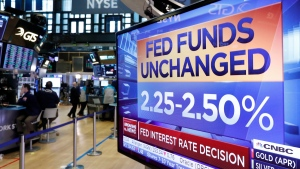 A screen on the floor of the New York Stock Exchange shows the rate decision of the Federal Reserve, Wednesday, March 20, 2019. (AP Photo/Richard Drew)