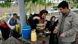 FILE -- An Iranian woman prepares tea during a relatives gathering marking the ancient festival of Sizdeh Bedar, the last day of the two-week Persian New Year holidays, at the Pardisan Park in Tehran, Iran, Tuesday, April 1, 2008. (AP Photo/Vahid Salemi)