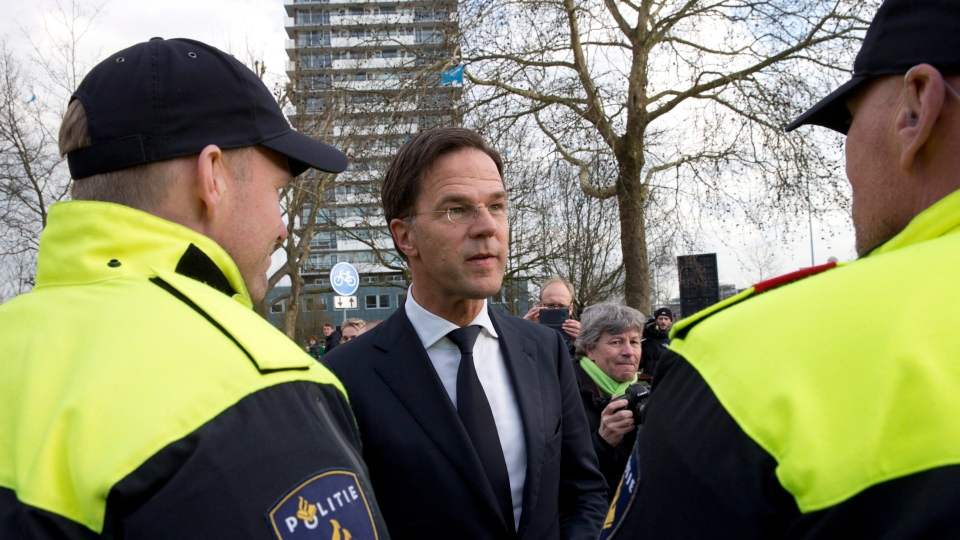 Dutch Prime Minister Mark Rutte expresses his gratitude to Dutch police officers after laying flowers at a makeshift memorial for victims of a shooting incident in a tram in Utrecht, Netherlands, Tuesday, March 19, 2019. A  (AP Photo/Peter Dejong)