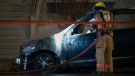 A firefighter pours water into a car that was destroyed by an arsonist in Montreal on March 21, 2019 (CTV Montreal/Cosmo Santamaria)