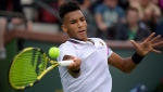 Felix Auger-Aliassime, of Canada, returns a shot to Yoshihito Nishioka, of Japan, at the BNP Paribas Open tennis tournament Monday, March 11, 2019, in Indian Wells, Calif. (AP Photo/Mark J. Terrill)