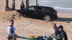 In this Wednesday, March 20, 2019 photo, rescue workers carry an injured child off the beach at Ormond-by-the-Sea, Fla. The Florida Highway Patrol says a sport-utility vehicle driven by 82-year-old William Johnson ripped through a wooden barrier separating a parking lot from the beach and hit four children in the sand. (David Tucker/The Daytona Beach News-Journal via AP)