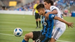 Vancouver Whitecaps' David Norman Jr., right, and Montreal Impact's Ken Krolicki battle for the ball during first half Canadian Championship action, in Montreal on Wednesday, July 18, 2018. (THE CANADIAN PRESS / Peter McCabe)