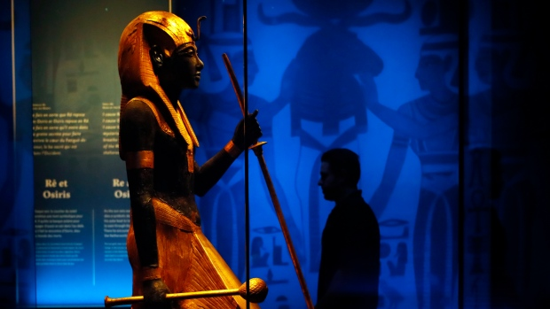 A visitor walks by a wooden guardian statue of the Ka of the king wearing the Names Headcloth displayed as part of 'Tutankhamun, the treasure of the Pharaoh', an exhibition in partnership with the Grand Egyptian Museum at the Grande Halle of La Villette in Paris, France, March 21, 2019. (AP Photo/Francois Mori)