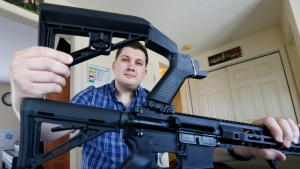 In this March 15, 2019 photo, Ryan Liskey displays a bump stock on top of his AR-15 at his home in Harrisonburg, Va. (AP Photo/Steve Helber)