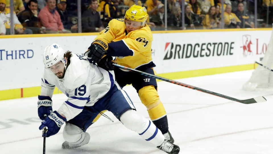 Nashville Predators center Mikael Granlund (64), of Finland, checks Toronto Maple Leafs center Nic Petan (19) in the third period of an NHL hockey game Tuesday, March 19, 2019, in Nashville, Tenn. The Predators won 3-0. (AP Photo/Mark Humphrey)