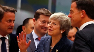 British Prime Minister Theresa May, center, speaks with Dutch Prime Minister Mark Rutte, right, and Luxembourg's Prime Minister Xavier Bettel, left, during a round table meeting at an EU summit in Brussels, Thursday, March 21, 2019.  (AP Photo/Frank Augstein)