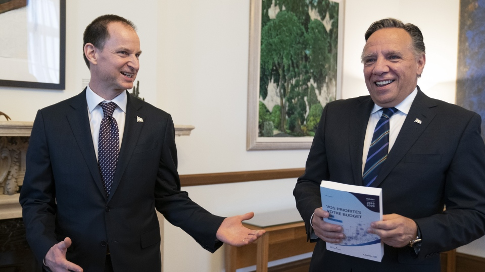 Quebec Premier Francois Legault receives a copy of the budget speech from Quebec Finance Minister Eric Girard, left, Thursday, March 21, 2019 at the premier's office in Quebec City. Girard will table his first budget since the election of a CAQ government. THE CANADIAN PRESS/Jacques Boissinot