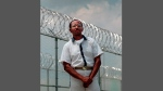 In this May 24, 1999 file photo, convicted killer Wayne Williams poses along the fence line at Valdosta Sate Prison, Valdosta, Ga. (AP Photo/John Bazemore, File)