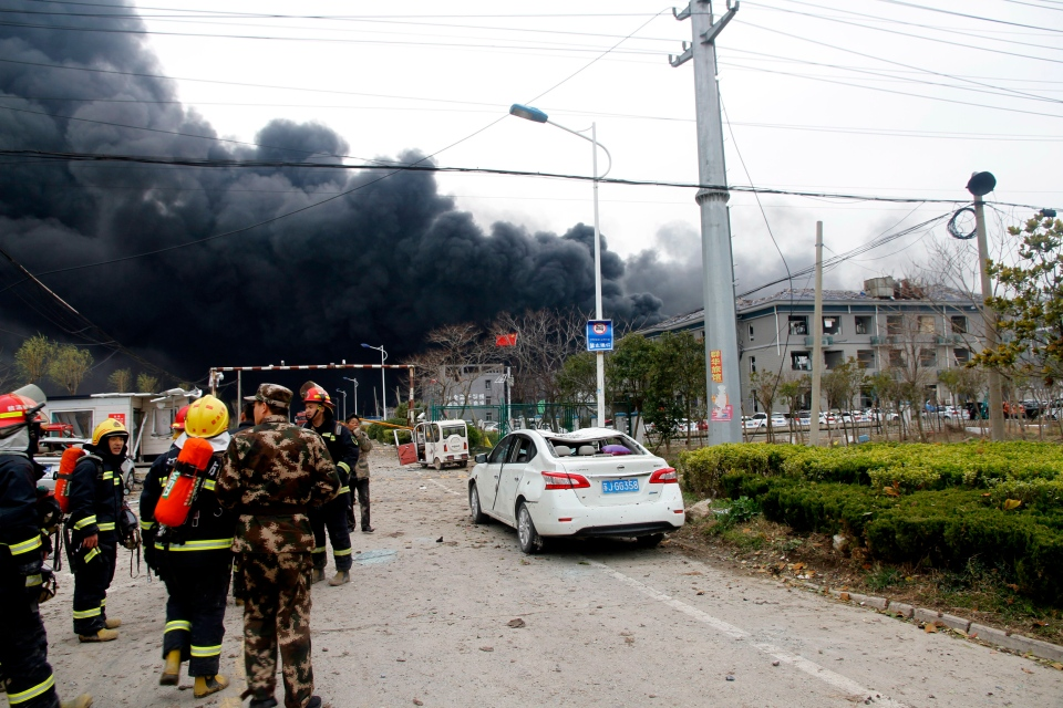 In this Thursday, March 21, 2019, photo, rescuers walk near the site of a factory explosion in a chemical industrial park in Xiangshui County of Yancheng in eastern China's Jiangsu province. (Chinatopix via AP)