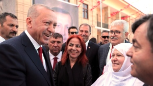 Turkey's President Recep Tayyip Erdogan chats with supporters of his ruling Justice and Development Party before a rally in Eskisehir, Turkey, Thursday, March 21, 2019. Erdogan has again screened clips of a video taken by the Christchurch mosque gunman, a day before the foreign minister of New Zealand - which is trying to stop its use - is due in Turkey.(Presidential Press Service via AP, Pool)