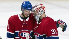 Montreal Canadiens' Brett Kulak congratulates goaltender Carey Price after shuttingout the New York Islanders 4-0 during NHL hockey action in Montreal on Thursday, March 21, 2019. THE CANADIAN PRESS/Paul Chiasson