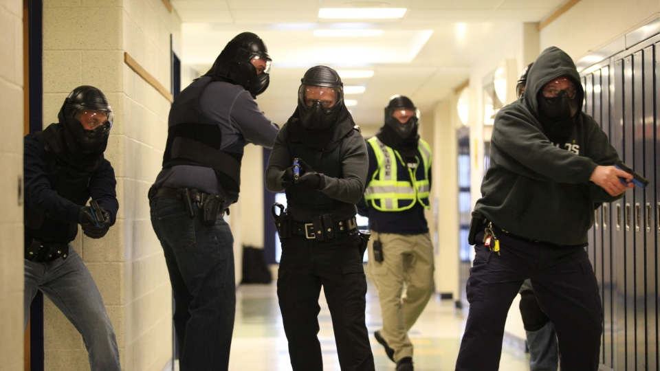 This file photo shows law enforcement officials involved in a drill are followed by an observer (yellow vest) to review with them what was done right or wrong once the scenario is completed. In this scenario a shooter is inside a school. (AP Photo/The Record, Kevin R. Wexler)