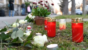 Flowers lay on the sidewalk where a 7-year old boy was stabbed on his way back from school in the Sankt Galler Ring area of Basel, Switzerland, (Georgios Kefalas/Keystone via AP)