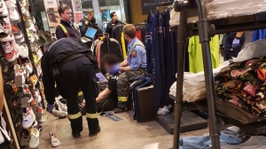 First responders tend to an injured man's neck at a Polo Park Foot Locker Thursday night. (Source: Dakotah Guiboche).