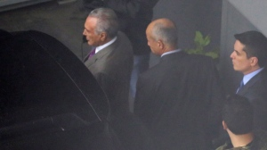 In this photo shot through a fence, former Brazilian President Michel Temer, left, is seen at the international airport in Sao Paulo, Brazil, Thursday, March 21, 2019. (AP Photo/Nelson Antoine)