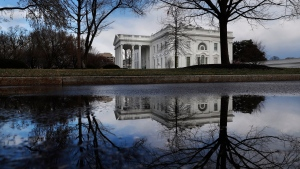 The White House is reflected in a puddle, Friday March 22, 2019, in Washington, as news breaks that the special counsel Robert Mueller has concluded his investigation into Russian election interference and possible coordination with associates of U.S. President Donald Trump. (AP Photo/Jacquelyn Martin)