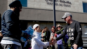 Omar Jammal, 9, shakes hands with Shane Muldrew as people gather with the Sikh Youth of Victoria during a protective human chain around Masjid Al Iman mosque as a show of love and solidarity with Muslim members during prayer at the mosque in Victoria, B.C., on Friday, March 22, 2019. THE CANADIAN PRESS/Chad Hipolito