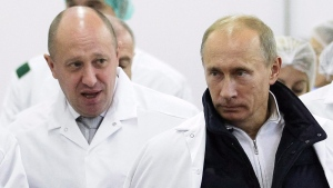 In this Monday, Sept. 20, 2010 file photo, businessman Yevgeny Prigozhin, left, shows Russian President Vladimir Putin, around his factory which produces school means, outside St. Petersburg, Russia. (Alexei Druzhinin/Pool Photo via AP, File)